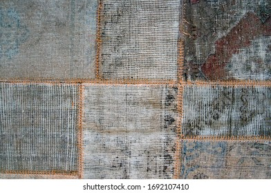 Background of patches of old carpets sewn together with orange jute thread.