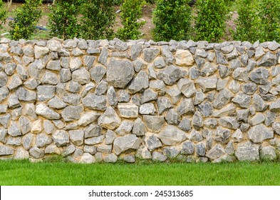 background pattern gray color of modern style design decorative fence real stone wall surface with cement on green grass field