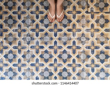Background and Pattern : Woman's feet on the old weathered dirty of vintage ceramic tiles floor on street in Thailand