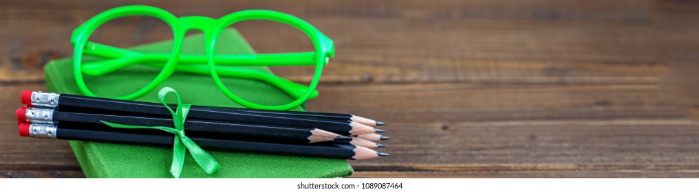 Background with pencils and glasses and a book. Banner for website. The concept is back to school.