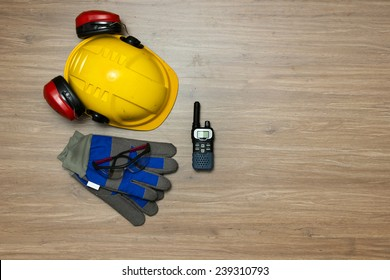Background of personal safety accessories on a wooden surface. Items include a hard hat with ear protection attached, safety goggles, working gloves and a cb radio