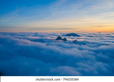 Background photo of low clouds in a mountain valley, vibrant blue and orange sky. Sunrise or sunset view of mountains and peaks peaking through clouds. Winter alpine like landscape of high Tatras.