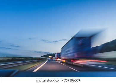 Background photograph of a highway, trucks on a highway, motion blur, light trails. Evening or night shot of trucks doing transportation and logistics on a highway.
