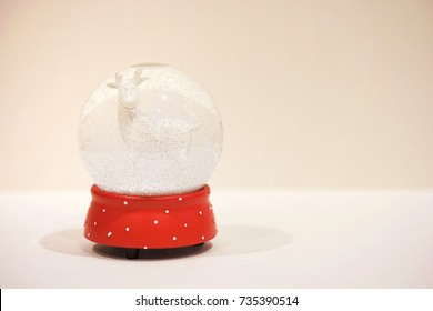 A background photograph of white and red christmas snow globe with white deer inside places at the left side and a white clear space