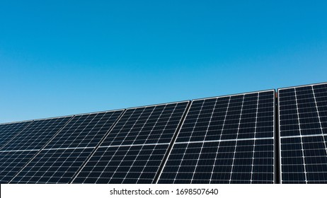 Background of photovoltaic modules for renewable energy. Huge solar panels with clear blue sky/