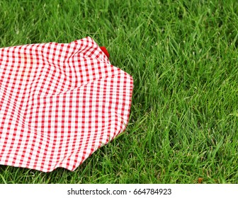 Background for a picnic - plaid on green grass