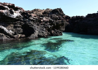 Background picture of black, rocky cliffs and turquoise, crystal clear water