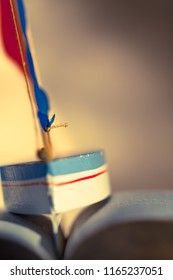 Background picture blurred with small detail of toy sailboat between the wavy pages of open book (copy space)/Sailing Trip Through Book