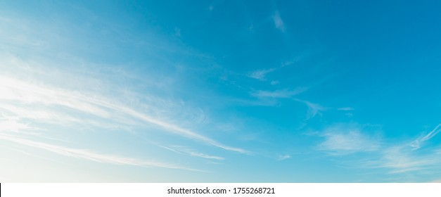Background picture low angle of bright blue sky on a sunny day. There are fluffy white clouds and clear. Blue and white color contrast in soft tones. Feeling fresh and relax. There is a copy space. - Shutterstock ID 1755268721