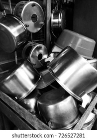 Background picture of unused stainless steel pots and pans on old wooden shelve.