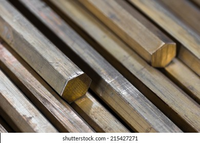 background of a pile of brass hexagonal rods closeup