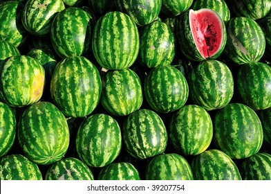 background of pile of fresh watermelon stacked and ready to sell.