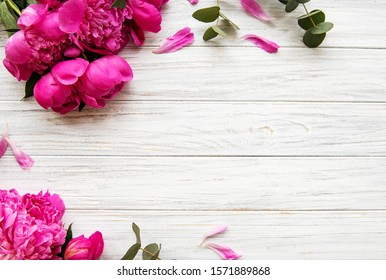 Background with pink peonies on old wooden board