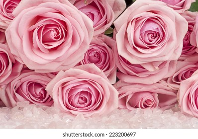 background of pink roses and quartz crystals
