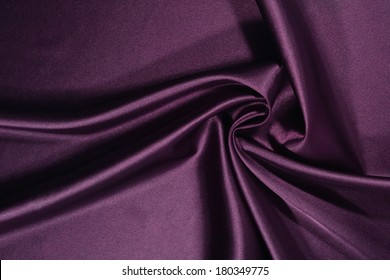 Background from a plum satin fabric with picturesque folds