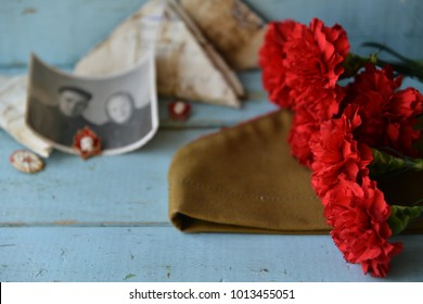 background for postcards by may 9, victory day: cap, letters, carnations and St. George ribbon