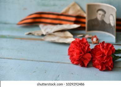 background for postcards by may 9, victory day: cap, letters, carnations and St. George ribbon Soviet icons and old photos