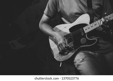 Background professional electronic guitar player strumming solo on stage in club, concert, music festival, new year party. Play punk rock and teaching tutorial band perform