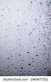 Background rain on the glass. Rain drops on window glasses surface with cloudy background . Natural Pattern of raindrops isolated on cloudy background.