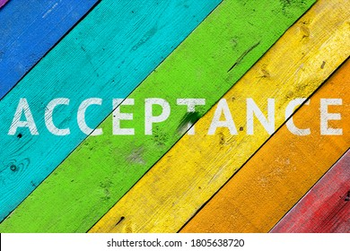 Background with a rainbow-colored LGBT community wooden surface with the words ACCEPTANCE. Concept - acceptance and agreement with LGBT people