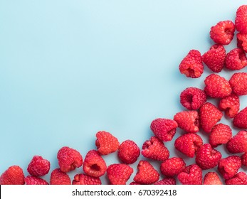 Background of raspberries. Raspberry on blue background with copy space. Isolated one edge. Summer and healthy food concept, Top view or flat lay.