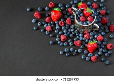 Background of raspberries, strawberry and blueberries. Berry on black background with copy space. Summer and healthy food concept, Top view or flat lay.