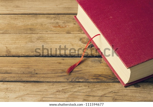 Background with red book and wooden deck table