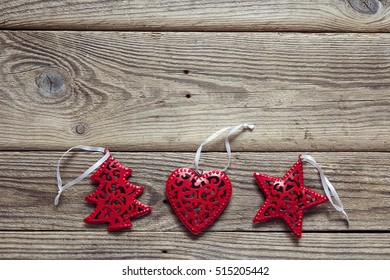 Background with red Christmas decorations on old wooden boards. Space for text.