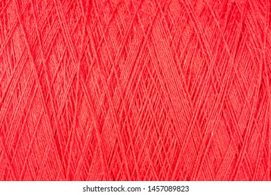 background of red cotton yarn on a cone