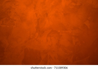 Background. Red, orange paint on the wall. Rough strokes of the master.