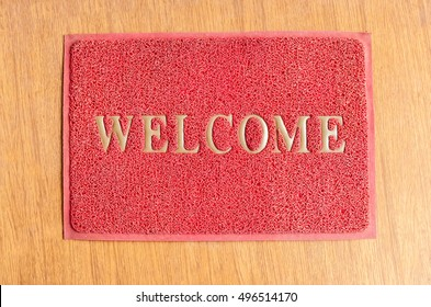 background of red welcome carpet on wood floor, (top view)