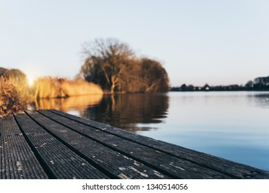 Background of relax chilling man sit waterfront drinking delicious hot coffee, tea under sun in winter spring cold weather. Enjoy and relax on his hobby listen music, read book after work on sunny day