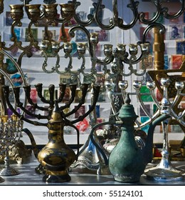 Background of the  retro and antique traditional Jewish holiday candlesticks with vintage jugs and old albums of stamps. Jerusalem flea market.