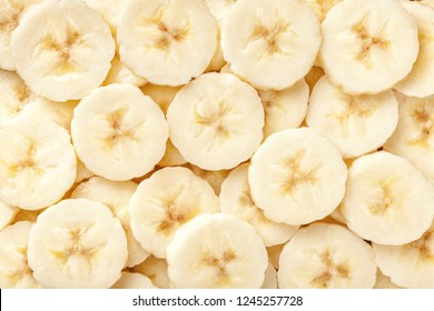 Background of ripe sliced banana slices, closeup. Food backdrop from fruit.