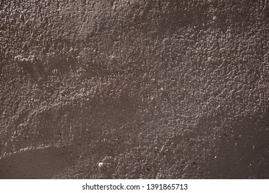 Background of rough uneven textured surface of concrete wall covered with plaster. Hard light.