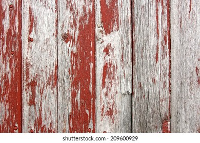 A background of rustic, aged barnwood boards, with peeling red paint.