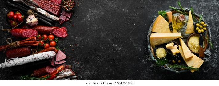 Background of salami, smoked sausage and assortment of cheese. On a black stone background. Free space for your text.