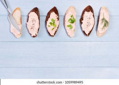 Background with salmon pate on pieces of various bread, blue wooden table. Top view.