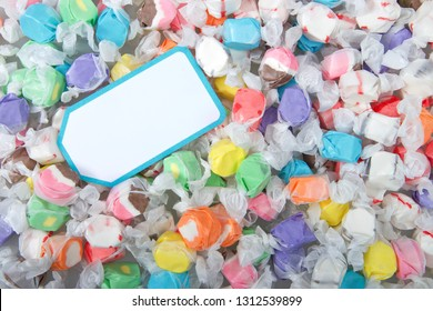 Background of salt water taffy in various flavors and colors wrapped in white transparent paper, blank card on top. Salt water taffy is sold widely on the boardwalks in the U.S. and Canada.