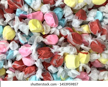Background of salt water taffy in various flavors and colors wrapped in white transparent paper, some leaking messy background. Salt water taffy is sold widely on the boardwalks in the U.S. and Canada