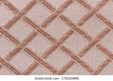 Background from a sample of furniture fabric brown and beige in macro. Cloth with a classic pattern in the form of crossed lines for upholstery of a sofa close-up.