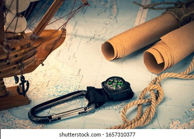 Background with a scroll of old paper, a magnetic compass, a sailboat and a geographical map.
