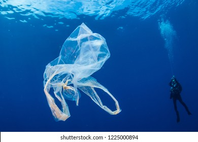 A background SCUBA diver next to a drifting, discarded plastic bag in a tropical ocean
