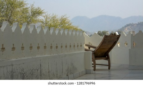 Background shot of a lounger chair on a balcony overlooking hills of Rajasthan, India.