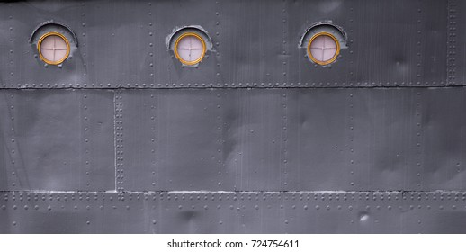 Background of the side of a naval ship, with three circular windows, interesting metal texture and patterns, suitable for design, space for words available.
