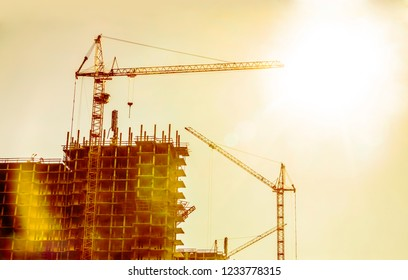 Background of silhouette building crane lift loads with sun set rays yellow cloudy evening sky backdrop. Construction site at orange sunset