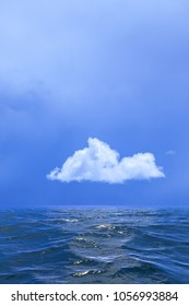 Background of sky and a single cloud reflected in water or ocean