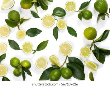 Background from a slices, whole of lime fruits with leaves isolated on white background.