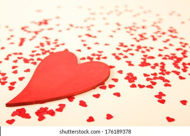 Background of small red hearts scattered on the yellow background