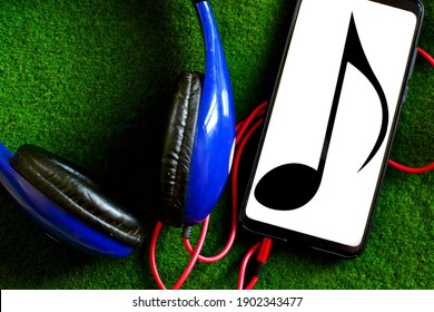 musiс background. Smartphone with note symbol on screen connected to headphones on green grass texture close up
